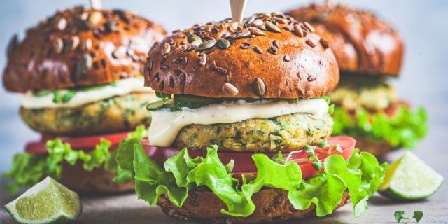 Vegan falafel burger with vegetables and sauce, dark background.